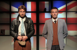 Les deux comédiens se tiennent debouts et statiques face à l'objectif avec le drapeau anglais sur un écran en fond de scène