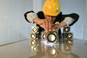Une personne, un casque de chantier sur la tête, installent des cubes transparents contenant un haut-parleur, sur une table