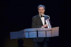 François Morel lit une partition tout en jouant du piano à bec