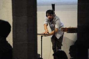 Un musicien, casque sur les oreilles, utilisent une sorte de tablette pour jouer de la musique