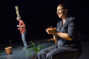 Le comédien tient une pile de brique en équilibre sur sa tête. La comédienne, assise au bord de la scène, l'applaudit.