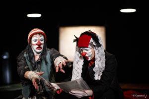 Deux clowns côte à côte lisent des papiers. L'un semble vouloir prendre les papiers des mains de l'autre
