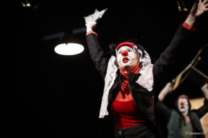 Une femme clown tend les bras au ciel