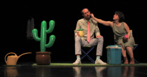 La comédienne pince la joue du comédien. Ils sont assis à côté d'un cactus vert.