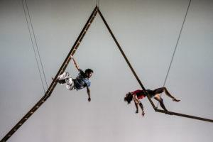 Un circassien se tient à une échelle pendue dans les airs et est rejoint par une trapéziste