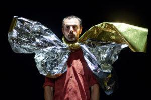 Le comédien porte un énorme noeud papillon en papier brillant