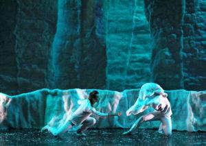 Les deux danseurs sont face à face, agenouillés, l'un avec un masque représentant peut-être un animal, l'autre lui tend la main, le tout dans un décor de glace