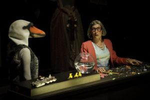 Une femme assise à une table regarde un énorme oiseau assis à ses côtés