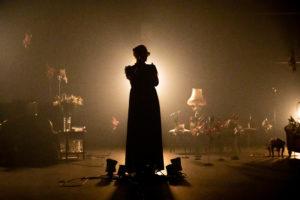 La comédienne chante en contrejour, on ne peut pas distinguer ses traits. c'est une silhouette noire sur un fond très lumineux et chaud du décor