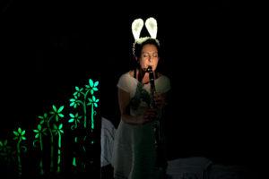 Une chanteuse s'approche tout près du micro pour chanter. Elle est dans le noi et porte un serre-tête avec des oreilles de lapin